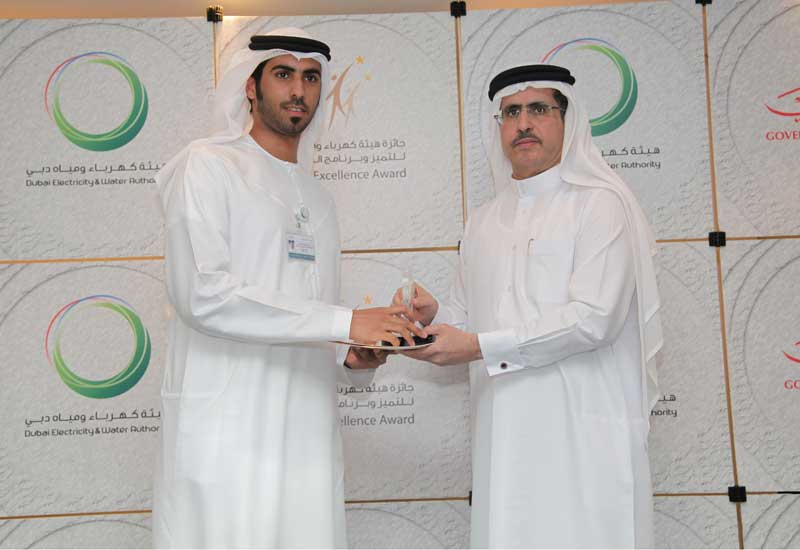 An employee receives his award from Saeed Mohammed Al Tayer (R).