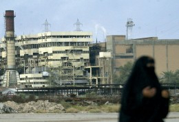 A woman walks past a Basra Electricity Company power plant that has seen better days.
